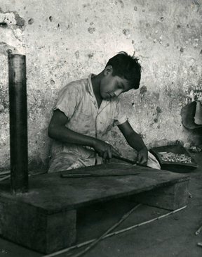 In this photograph a boy is shown cutting carrizo  into open ended tubes for cohete powder cases.
